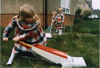 Image 07: Untitled (Girls in Plaid 'Hoovering' the Lawn)