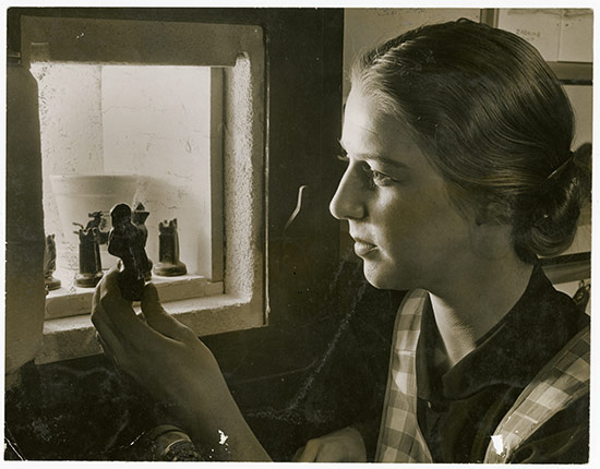Carol Janeway Holds a Chess Piece and Peers into Kiln, 1944